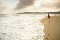 Beautiful young woman walks along the surf on a pristine sandy beach