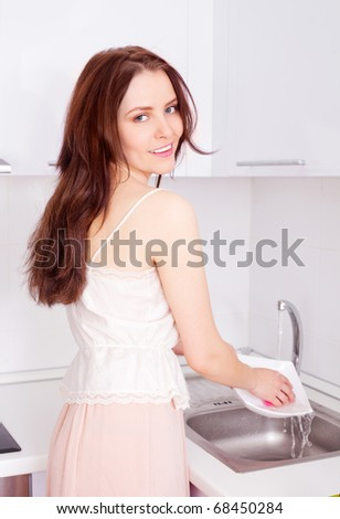 beautiful young woman washing dishes in the kitchen at home
