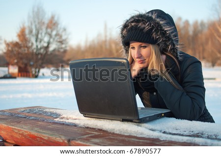 Beautiful young woman watching laptop sitting on a bench in winter surrounded by snow - stock photo