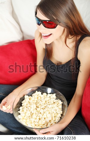 Beautiful young woman watching TV in 3d glasses and eating popcorn