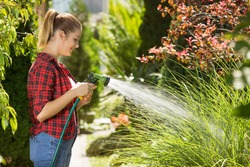Beautiful young woman watering garden