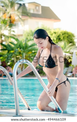 2be638bf98b Beautiful young woman wearing a black bikini swimsuit getting out of the  pool  494466109