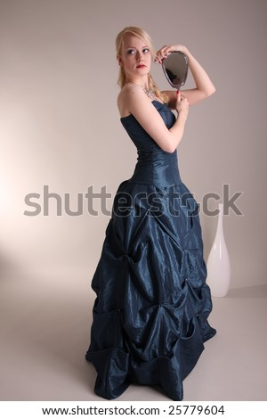 Beautiful young woman wearing a blue prom dress and silver mirror