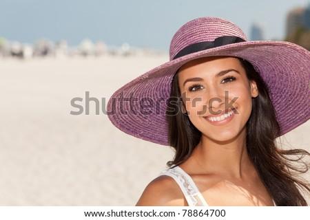 Beautiful young woman wearing a fancy purple hat and enjoying Miami's beautiful South Beach. - stock photo