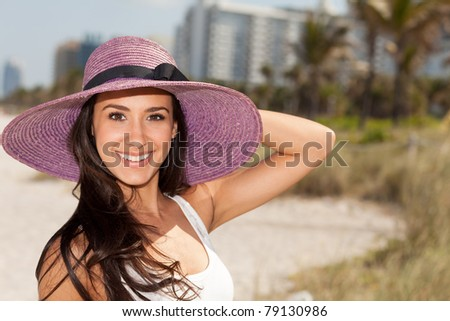 Beautiful young woman wearing a fancy purple hat and enjoying Miami's beautiful South Beach.
