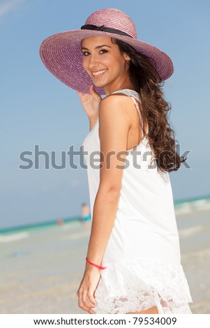 Beautiful young woman wearing a fancy purple hat and enjoying the pristine crystal clear shoreline of Miami's beautiful South Beach.