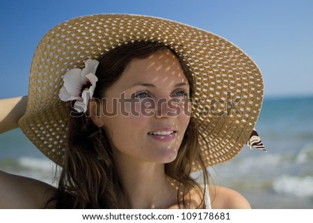 Beautiful young woman wearing a hat and a white dress enjoying the sun and the view of the sea