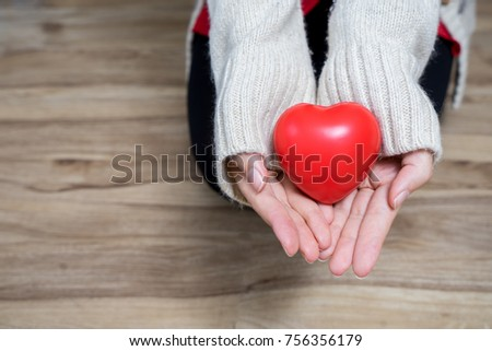 Beautiful young woman Wearing a Santa hat With Christmas trees Hold red heart in hand in festive season. #756356179