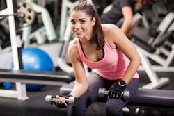 Beautiful young woman wearing a sporty outfit and gloves using dumbbells for her workout in a gym