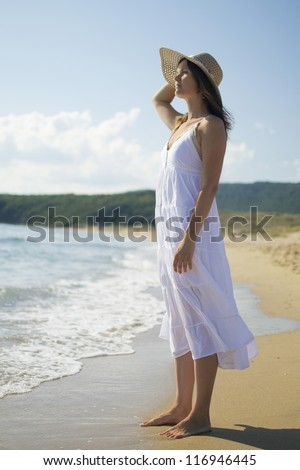 Beautiful young woman wearing a white dress and straw hat looking out to sea