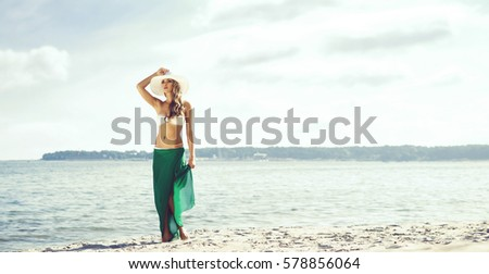 Beautiful, young woman wearing alluring bikini and green silk on the beach. Traveling, vacation, holiday, concept.