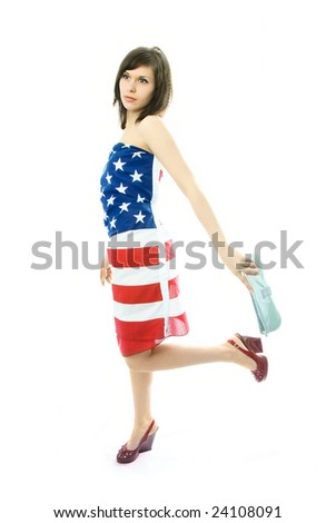 beautiful young woman wearing an American flag walks with a bag in her hand
