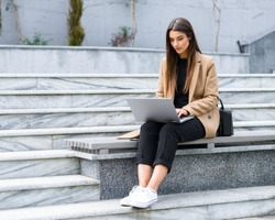 Beautiful young woman wearing autumn coat using laptop while sitting on a bench