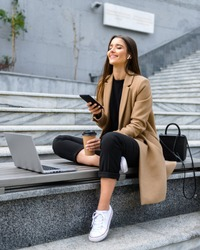 Beautiful young woman wearing autumn coat using laptop while sitting on a bench, holding mobile phone