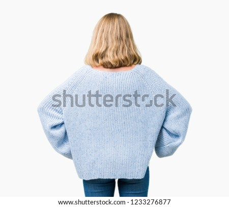Beautiful young woman wearing blue sweater over isolated background standing backwards looking away with arms on body