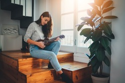 Beautiful young woman wearing casual clothes enjoying play ukulele guitar in the morning sitting on wooden stairs at home near big window, Flare Light, Happy lifestyle Leisure Activities Concept