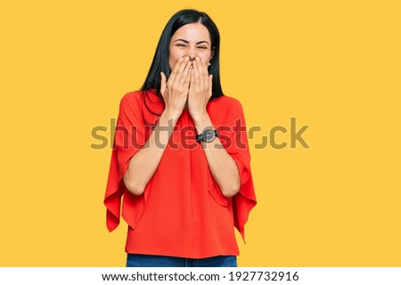 Beautiful young woman wearing casual clothes laughing and embarrassed giggle covering mouth with hands, gossip and scandal concept  ストックフォト ©