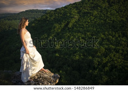 Beautiful young woman wearing elegant white dress standing on a rock overlooking mountains and green forests