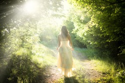Beautiful young woman wearing elegant white dress standing with a smile on a road in the forest with rays of sunlight beaming through the leaves of the trees