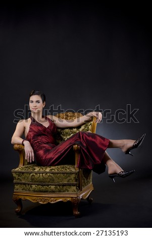 Beautiful young woman wearing evening dress lsitting in carved wood armchair, on dark background.