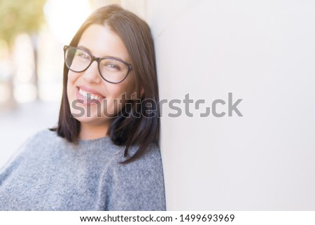 Beautiful young woman wearing glasses smiling cheerful leaning on wall, casual pretty girl at the town
