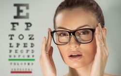 Beautiful young woman wearing glasses standing in front of eye test