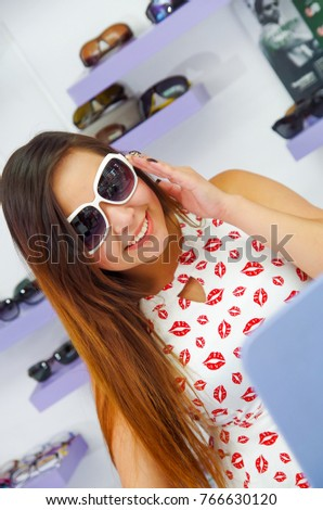 Beautiful young woman wearing huge sunglasses in optical store, in blurred background