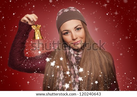 beautiful young woman wearing knitted clothes, ringing a christmas bell on red background - stock photo