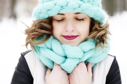 Beautiful young woman wearing merino wool pastel colors hat and scarf enjoying the fresh morning outdoors. Skin Care, Lip care, care of the eyelashes in the winter season.
