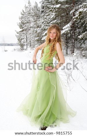 Beautiful young woman wearing prom dress in snowy setting