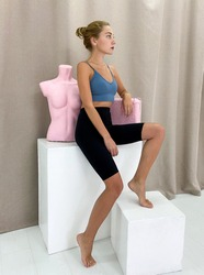 Beautiful young woman wearing sports bra and knee length leggings