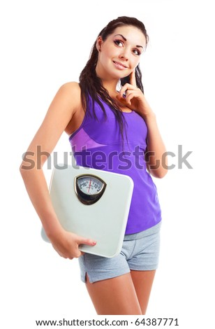 beautiful young woman wearing sports clothes holding scales