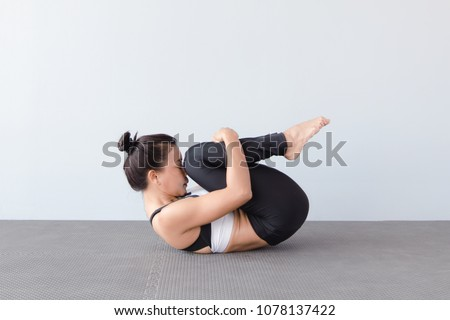 Beautiful young woman wearing sportswear practicing yoga in studio,natural light.Pavanamuktasana (Wind-Relieving Pose).Concept : yoga poses for beginner. #1078137422