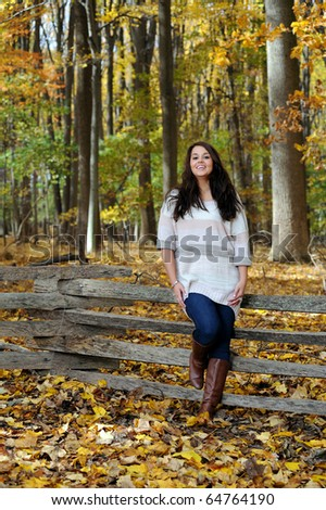 Beautiful young woman wearing sweater in autumn forest - resting on wood fence