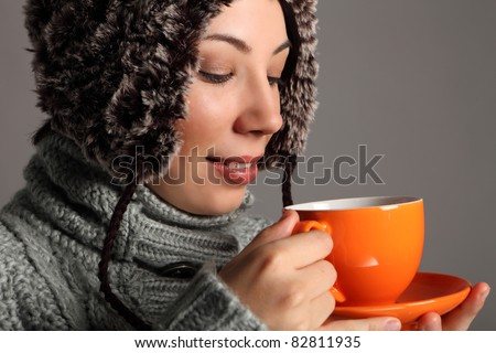 Beautiful young woman wearing thick wool sweater and furry winter hat, drinking tea from orange cup. Shot against a grey background.