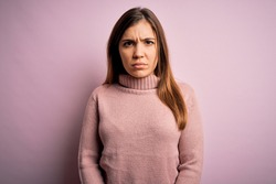 Beautiful young woman wearing turtleneck sweater over pink isolated background skeptic and nervous, frowning upset because of problem. Negative person.