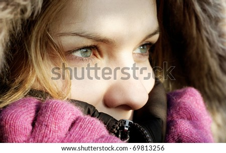 Beautiful young woman wearing winter jacket hood and gloves