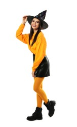 Beautiful young woman wearing witch costume for Halloween party on white background