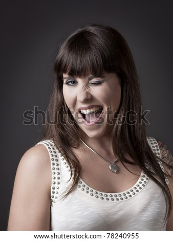 Beautiful young woman winking eyes against a grey background