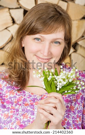 Beautiful young woman with a bouquet of lilies of the valley