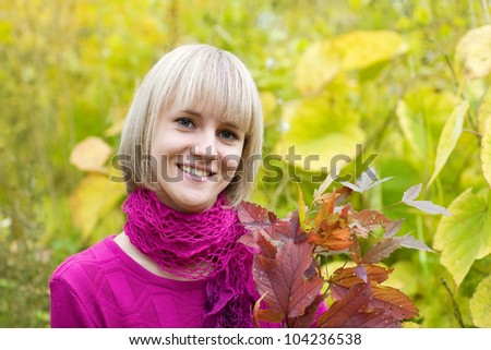 Beautiful young woman with a branch of the autumn foliage.