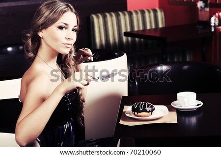 Beautiful young woman with a cup of tea at a caf
