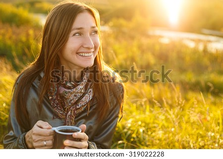 Beautiful young woman with a cup of tea outdoor.
