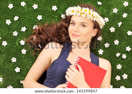 Beautiful young woman with a daisy hair wreath lying on a green grass with daisy flowers