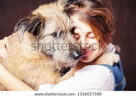 Beautiful young woman with a funny shaggy dog on a dark background. Love, care, friendship Foto stock ©