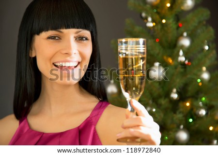 Beautiful young woman with a glass of champagne wishes you a holiday
