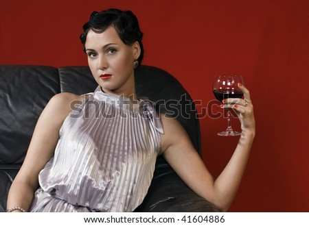 Beautiful young woman with a glass of wine. Studio shot in a retro style