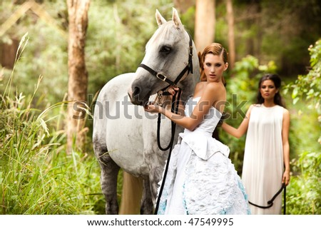 beautiful young woman with a grey horse in the rainforest