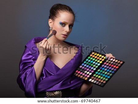 Beautiful young woman with a make-up holds a cosmetic palette. - stock photo