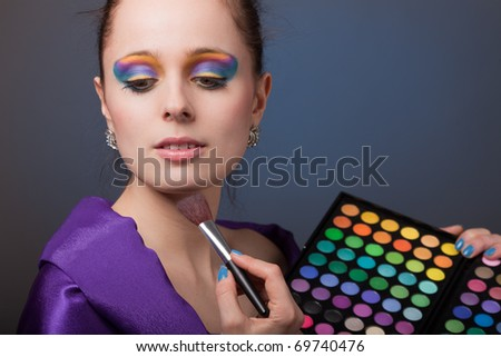 Beautiful young woman with a make-up holds a cosmetic palette.